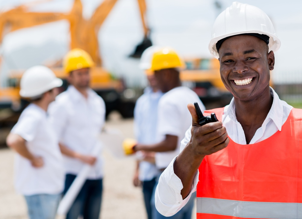 Construction worker talking on a radio and looking happy